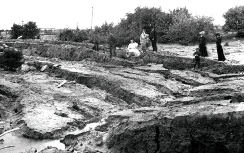 black and white photo of family standing on a ground that was damaged from liquefaction