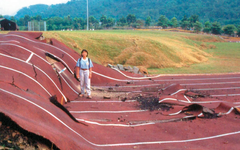 A Taiwan students standing on a school track that was completely destroyed by an earthquake