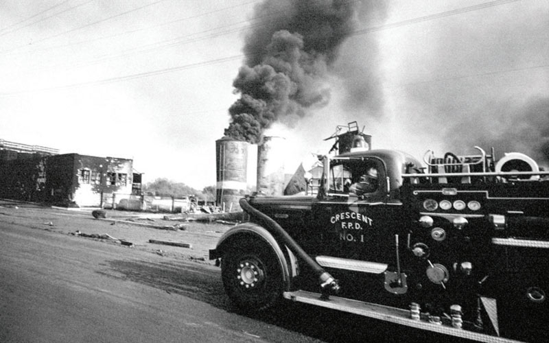 Crescent city fire truck from the 1960's with a large fire in front of them