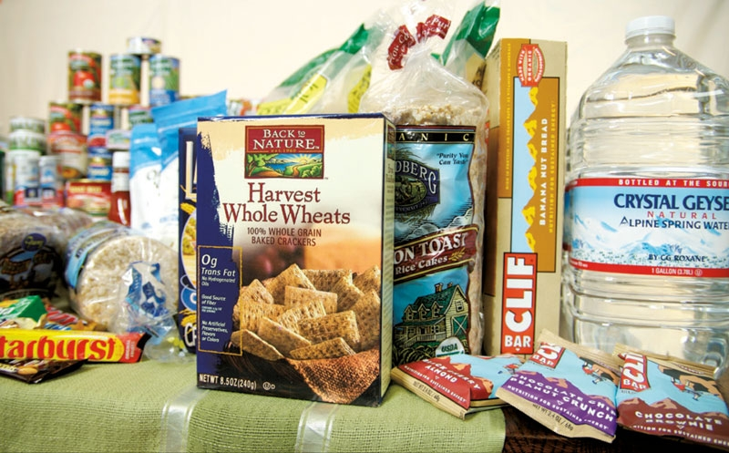 Food sitting on a table, rice cakes, clif bars, cracker, canned goods and water