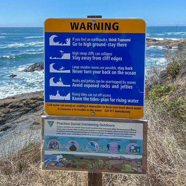 Tsunami Warning sign right next to the ocean/beach